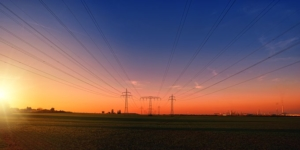 Picture of power lines on a field at sunset.